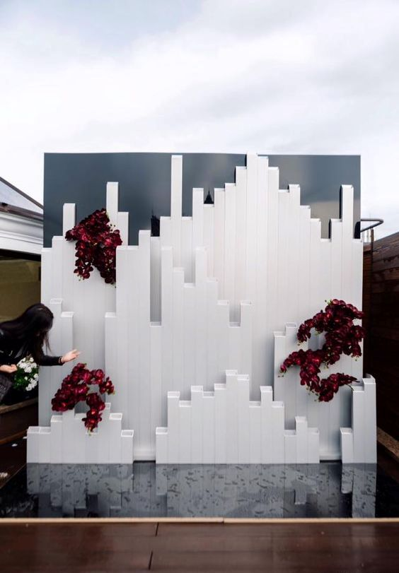 a bold minimalist wedding backdrop with burgundy orchids inspired by Icelandic landscapes is a fantastic idea for a minimalist wedding