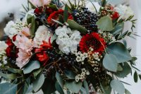 a bold wedding bouquet with white, pink and deep red blooms, waxflowers, berries and greenery for a colorful summer or fall wedding