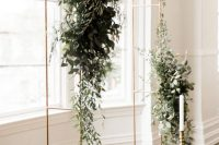 a brass minimalist wedding arch decorated with lush greenery and white blooms plus a single candle in a tall candlestick is awesome