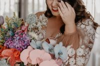 a bride rocking a fantastic iridescent statement wedding bouquet with colorful blooms, foliage and grasses for a wow factor