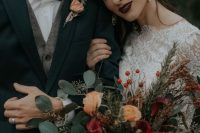 a bright Christmas wedding bouquet of deep red and yellow blooms, greenery, grasses and berries is a gorgeous idea for a holiday celebration