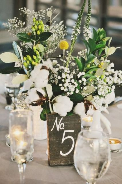 a bright and relaxed wedding centerpiece of greenery, cotton, billy balls and white blooms plus a reclaimed wood number