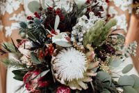 a bright fall wedding bouquet of pink and white king proteas, greenery and dark foliage, berries, thistles and various textural elements is wow