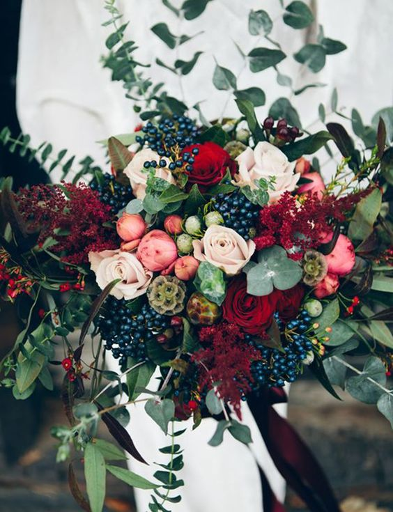 a bright fall wedding bouquet of pink, deep red and blush blooms, greenery and dark foliage, berries and seed pods looks very spectacular and will make a statement