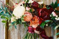 a bright fall wedding bouquet of white, orange, fuchsia and blush blooms, greenery and some privet berries is amazing for a bold fall wedding