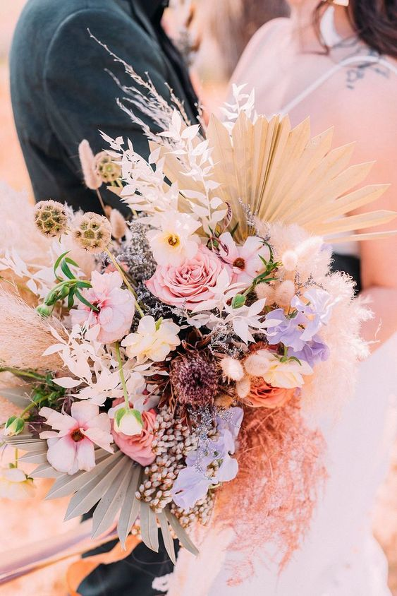 a bright iridescent wedding wedding bouquet of pink, neutral and lilac blooms, dried foliage, seed pods and fronds is wow