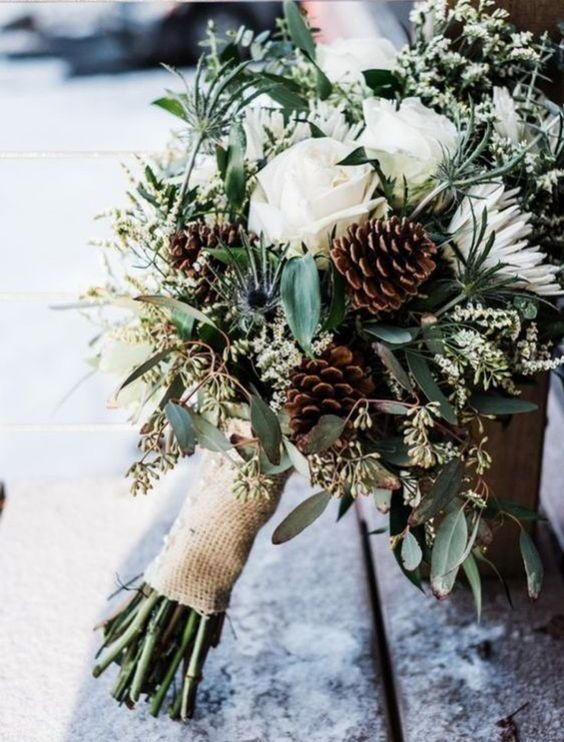 a casual and rustic winter wedding bouquet of white blooms, pinecones, eucalyptus, burlap is a lovely idea for a rustic wedding