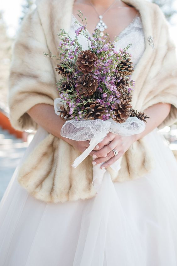 a catchy organic wedding bouquet of pinecones and lilac blooms in a tulle wrap is a stylish idea for a winter wedding