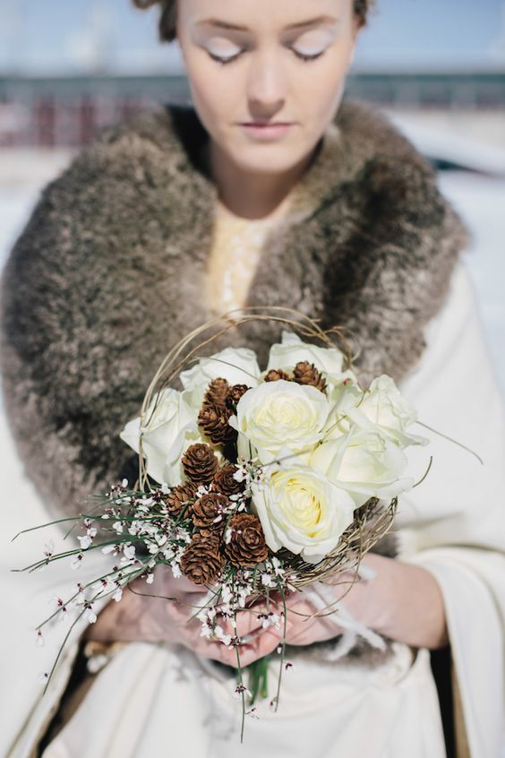 a catchy winter wedding bouquet of white roses, pinecones and small white blooms, twigs and a vine wrap is all cool