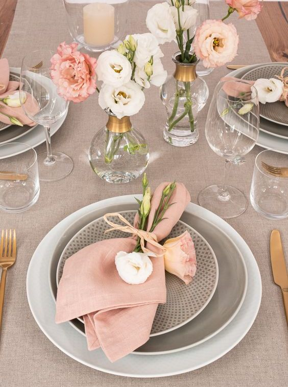 a chic and delicate wedding tablescape done with greige linens and plates, with pink napkins and blooms and gold cutlery is chic