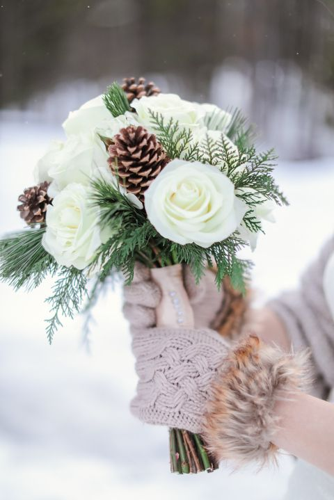 a chic and neutral wedding bouquet of white roses, fern and greenery plus pinecones is a gorgeous idea for a rustic winter wedding