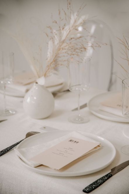 a chic minimalist and neutral wedding tablescape with dried grasses in white vases, white plates and neutral menus and catchy cutlery