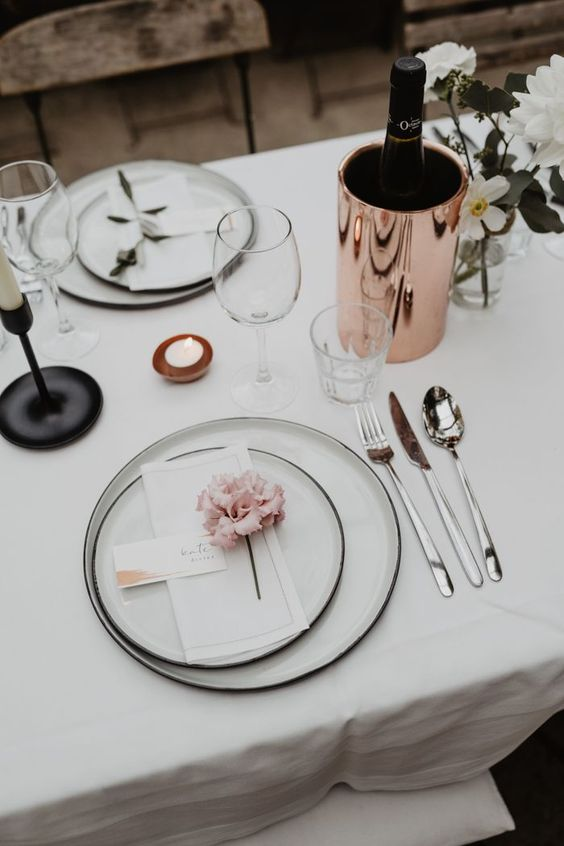 a chic minimalist wedding tablescape with elegant white linens, white plates with black edges, white blooms and candles