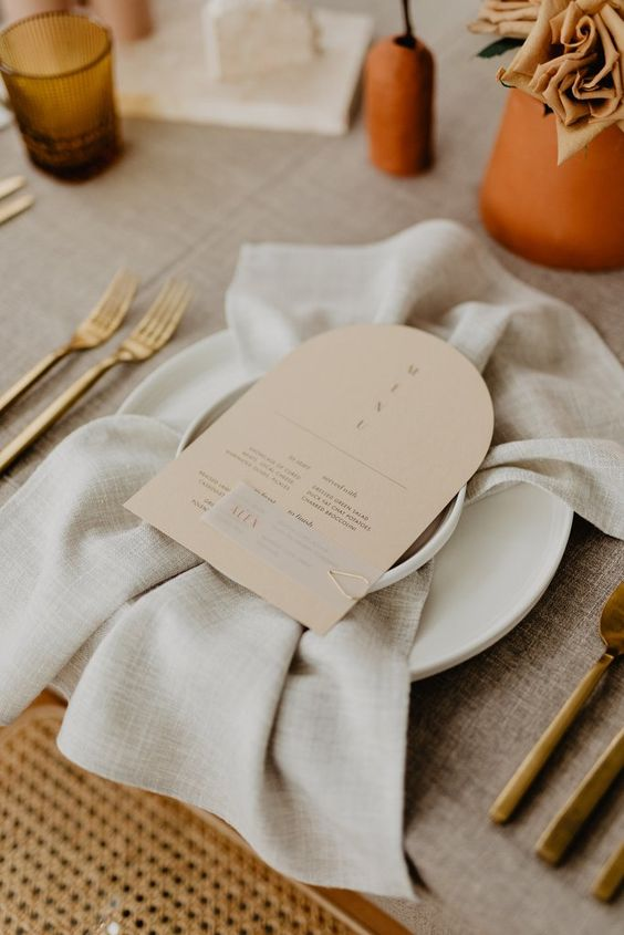a chic wedding tablescape with a greige tablecloth and greige menus, gold cutlery, terracotta vases and dusty blooms