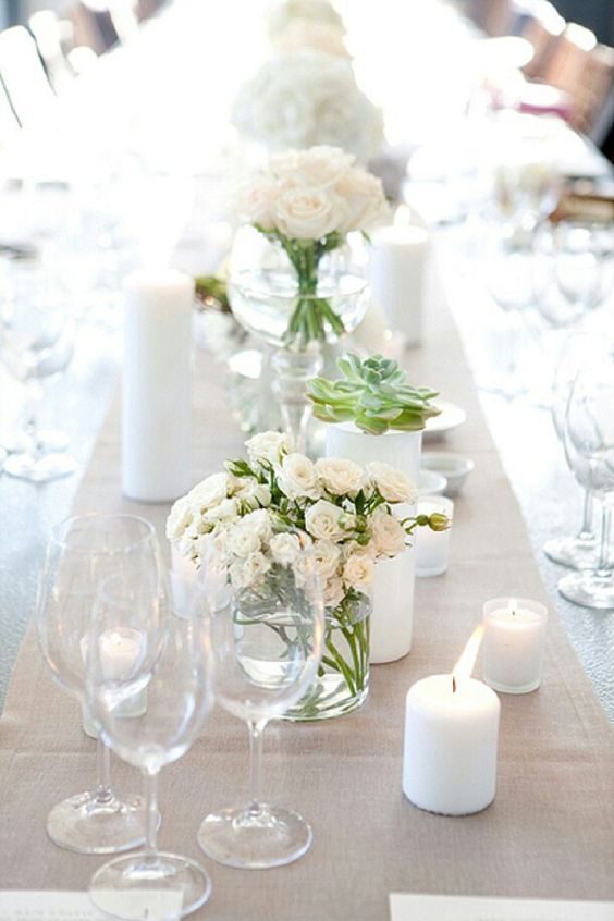 a chic wedding tablescape with a white tablecloth, white pilalr candles, white blooms, succulents and a pretty greige table runner for an eye-catchy touch