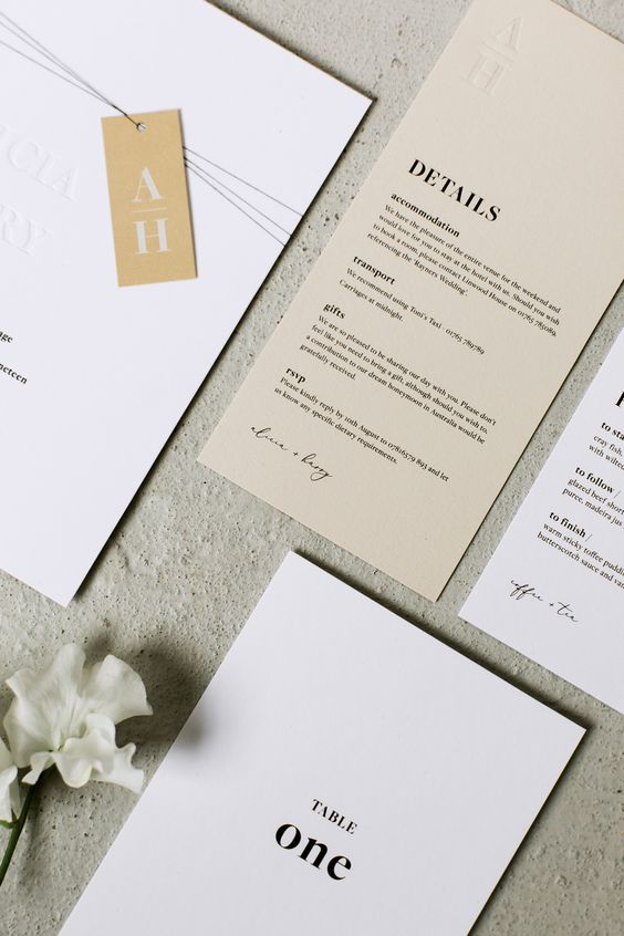 a chic white and tan wedding invitaiton suite with black letters and monogram tags is a cool idea for a minimalist wedding, and with plenty of detail