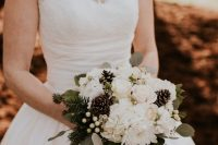 a chic winter wedding bouquet of white blooms, greenery, evergreens, berries and pinecones is a traditional idea for an elegant winter wedding