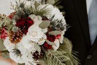 a classic winter wedding bouquet of white and red roses, evergreens, thistles, pinecones and greenery is timeless for a winter bride