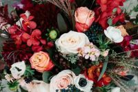 a colorful fall wedding bouquet of burgundy and deep red blooms, white and blush ones, various berries, foliage and grasses is super cool