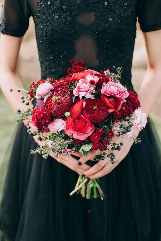 a colorful fall wedding bouquet of red, pink and burgundy blooms, greenery and privet berries is a bold touches to a Halloween or fall bridal look