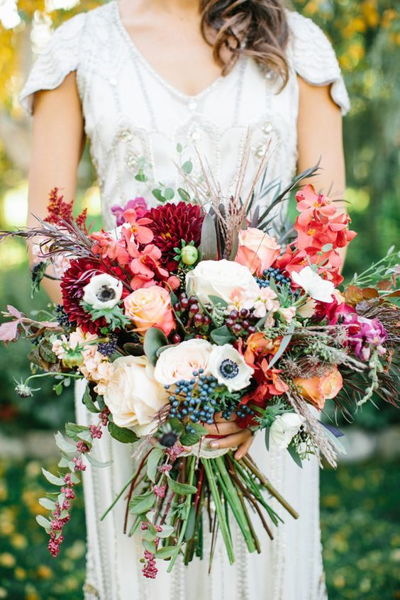 a colorful fall wedding bouquet of white, deep red, fuchsia, orange and yellow blooms, greenery and cascading touches, grasses and berries