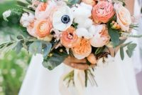 a colorful garden wedding bouquet of coral, peachy, blush blooms, white anemones, cotton, greenery and twigs is a beautiful idea
