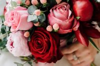 a colorful wedding bouquet of deep red and pink roses and peonies, of berries and eucalyptus is amazing for a summer wedding