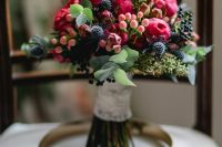 a colorful wedding bouquet of pink blooms, berries, thistles and greenery is a lovely idea for a summer or fall wedding