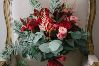 a colorful wedding bouquet of red and pink blooms, berries and various types of greenery for a Christmas wedding