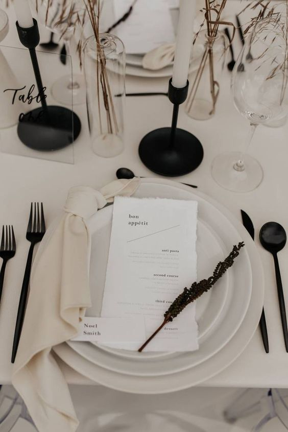 a contrasting minimalist wedding tablescape with neutral plates, black cutlery candlesticks and dried blooms and grasses