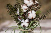 a cool fall or winter wedding centerpiece with eucalyptus, cotton and grass in a mason jar for a cozy relaxed wedding