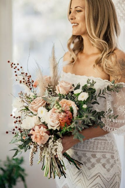 a cool pastel wedding bouquet of white, blush and pink blooms, greenery, berries and thistles for more texture for a fall bride