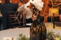 a cozy winter centerpiece with snowy pinecones, evergreens, candles, cottons and wine bottles with branches and faux snow around it