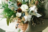 a creative fall wedding bouquet of white blooms, leaves, thistles, foliage, fern, berries, cotton and twigs for a boho fall bride