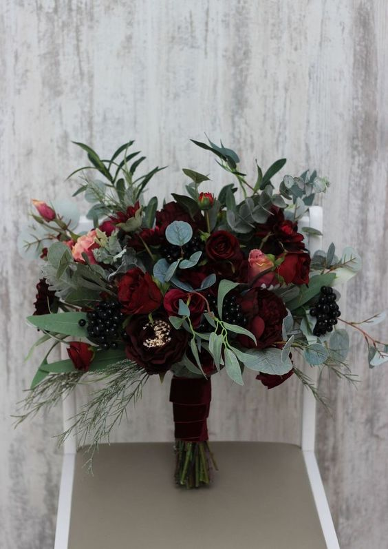 a dark wedding bouquet of burgundy and deep red blooms, berries and lots of textural greenery is great for both moody fall and winter weddings
