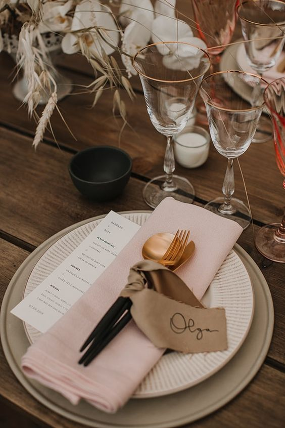 a delicate and lovely wedding tablescape with white orchids and dried grasses, greige placemats, white plates and pink napkins