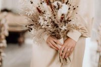 a delicate dried wedding bouquet of cotton, bunny tails, berries, twigs, dried foliage and grasses plus ribbons is ideal for fall