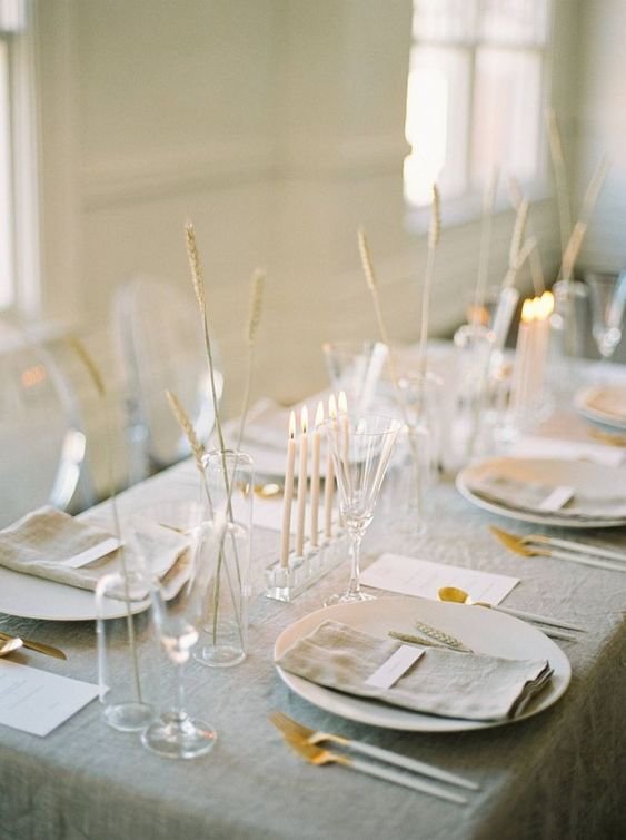 a delicate minimalist wedding tablescape with a grey tablecloth and napkins, white chargers and cutlery, some grasses in vases and tall and thin candles