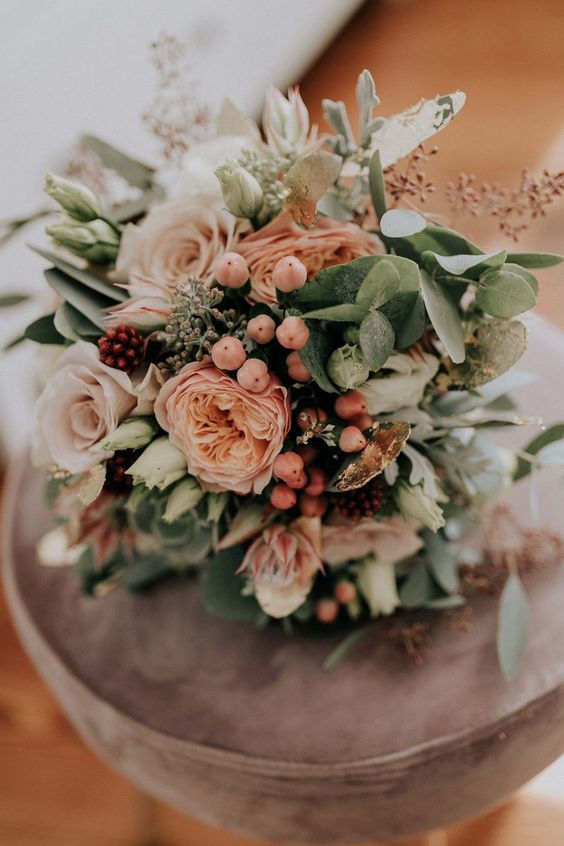 a delicate pastel wedding bouquet of pink and blush blooms, greenery and various berries will work for a summer wedding