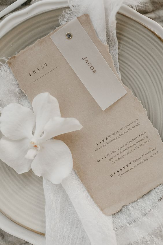 a delicate place setting with greige plates and a greige menu with a raw edge plus neutral linens is a lovely idea