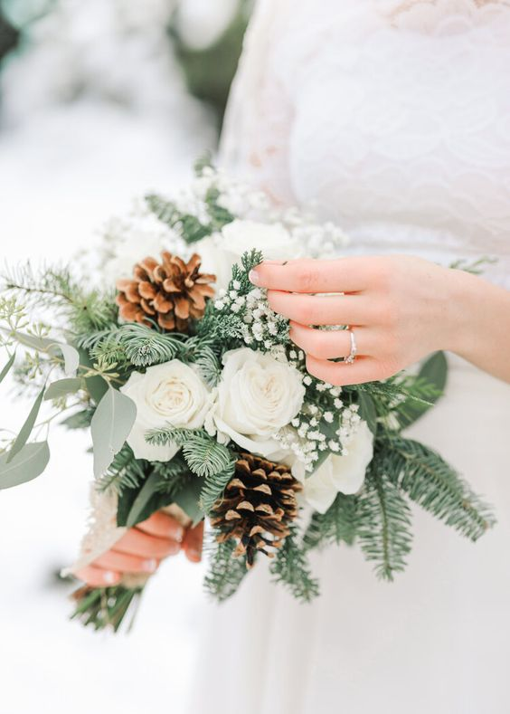 a delicately and lovely winter wedding bouquet of white roses, baby's breath, evergreens and eucalyptus is an amazing winter idea