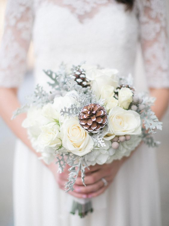 a dreamy neutral wedding bouquet of white blooms, snowy pinecones, berries is a lovely idea for a neutral winter wedding