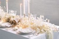 a dreamy wedding table runner with lots of white blooms, cascading touches, lunaria and other dried elements is a gorgeous idea for an ethereal spring wedding
