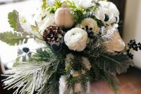 a dreamy winter wedding bouquet of evergreens, pale leaves, white anemones and ranunculus, privet berries, thistles and snowy pinecones