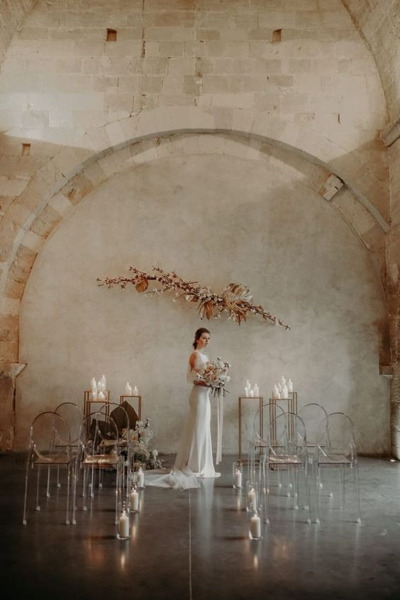 a fantastic minimalist wedding space with a blooming branch arrangement and candles for the altar plus ghost chairs lined up with candles