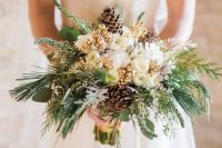a glam and shiny winter wedding bouquet of white blooms, gilded berries, pinecones, evergreens and greenery is a lovely idea