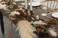 a gorgeous boho wedding table runner of magnolia leaves, pampas grass, cotton, with thin tall candles and with ribbons is super chic