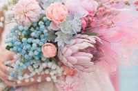 a gorgeous iridescent wedding bouquet with blue and pink blowers and dried and spray painted ones is a beautiful idea to rock