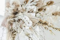 a gorgeous long stem wedding bouquet that includes a lot of cotton, dried blooms, grasses and branches is a gorgeous idea for a boho bride
