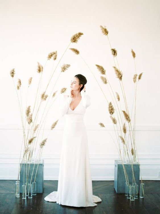 a gorgeous minimalist wedding altar of grasses inserted into cinder blocks and simple glasses is a lovely idea for a minimalist fall wedding